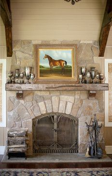 stone fireplace with rustic wood mantel which holds a horse painting and a silver trophy collection - Bruce Kading Interior Design, brucekading.com - Photo by Shelly Mosman