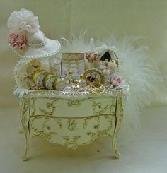 """Another wonderful creation from Vicky of """" Secrets"""" Ladies Cream with gold detail Bombe Chest. It has been carefully dressed with a beautifully made ladies items including, necklace, feather boa, toiletries etc. The drawers have also been filled with ladies lingerie items. Everything is fixed in place."""