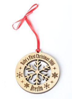Personalized Babys First Christmas Ornament with a silhouette of a snowflake cut…