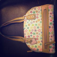 "Dooney and Bourke White Purse with Stars Rarely used and always stored in original fabric bag, 5""X11"" base 7"" tall with 8"" tall straps, white back ground with multi colored stars and light tan straps Dooney & Bourke Bags"