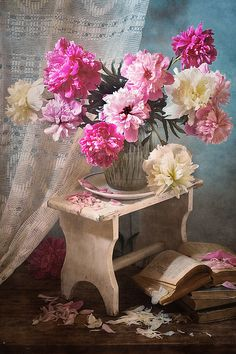 http://pixels.com/products/bouquet-of-peonies-on-white-tabouret-nikolay-panov-art-print.html floral still life photography with lush bouquet of pink and white peonies in vase on rustic tabouret and old vintage books on wooden floor in village in summer