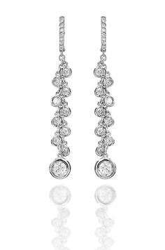 """Let diamonds cascade from your ears in Haute Vault's 18K white gold and diamond earrings. With nine bezel-set diamonds and one larger diamond to finish the piece, you will want to pull your hair back for a sexy and sophisticated look. Measures 2 1/4"""" long"""