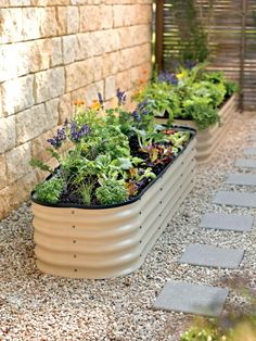 This modern trough-style planter can be placed in gardens, and along driveways and walkways to grow flowers, herbs and vegetables. The raised planter, made of Zincalume steel and sold by Gardener's Supply, is 15 inches high.