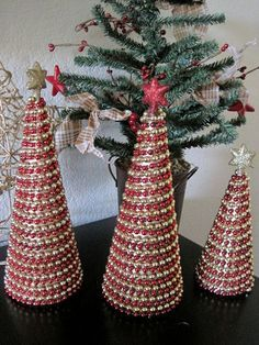 Thinking ... Green Styrofoam Cones, Covered with Gold or silver wrapping paper, then wrapped the beads around (alternating colors). Could just use a pin at the beginning or end of the beads with the styrofoam ..: