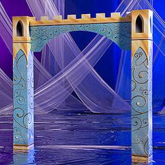 Our Fairytale Castle Arch features gold swirls on the light blue speckled background.