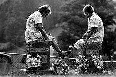 David Turnley: Two elderly women visiting the graves of their parents in the Appalachian Mountains sit on the headstones and talk. 1983