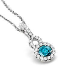 Mesmerizing 1/2 ct Center Blue Diamond Pendant with Surrounding Sparkling White Diamonds set in 14k White Gold in a Delicate Design.