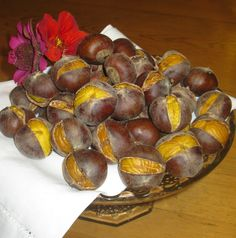 Perfect Roasted Chestnuts (2nd best to fireplace cookin'). Cut slash across the side opposite eye of chestnut (i.e., diag). Place in pan of lightly salted, hot water (I put lots of salt b/c...I felt like it?!). Cover & simmer 10-15 min. Don't boil (I did for a few min & they still came out well!). Preheat oven to 375 degrees. Drain chestnuts. Place on ungreased cookie sheet & bake 14-16 minutes. Chestnuts will plump as they simmer, & slash will open during baking making it easy to peel and eat.