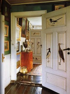 Raised-panel doors painted with bird portraits in the early 20th century by Michael Ancher.