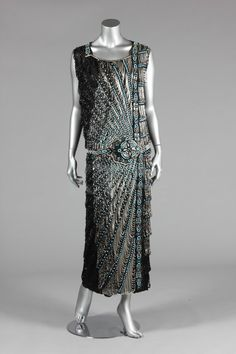 A good beaded flapper dress, circa the black chiffon ground adorned with an embroidered belt in silver and turquoise beads, silver looped swags cascade in bands down one side, black looped fringes cover the remainder of the ground, ankle length 1920 Style, Style Année 20, Flapper Style, Flapper Party, 20s Fashion, Art Deco Fashion, Fashion History, Retro Fashion, Vintage Fashion