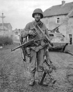 Robert Leigh, Private First Class (PFC) in the 83rd Infantry Division with his collection of captured German weapons taken during the Battle of the Bulge - 3 MP.40's and a MG.34 & MG42