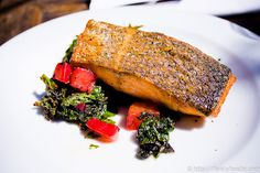 Pan seared Verlasso salmon with grilled mustard greens, beets & tomato vinaigrette