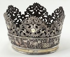 "In Eastern Europe's Galicia, this keter's inscription refers to Deuteronomy 32:11, ""As an eagle stirs up her nest, broods over her young…"" The animals on the crown's base represent those that would be sacrificed at the Temple. This silver folk-art crown was made during the 18th- to 19th Centuries and is part of the Michael Steinhardt Judaica Collection. I find it especially interesting because the double-headed eagle with a crown in the middle is also the Russian coat of arms"