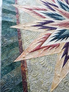 Feathered Star, Judy Niemeyer, at Mainely Quilts of Love. Glide thread in several colors was used.  The fills are dense to enhance the many circles added in the quilting for visual interest.  There are also feathers and line-work.  This represents 18-20 hours of quilting time.  It is a show quilt, and has won a 1st place and Best Machine quilting award to date.