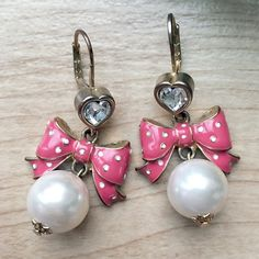 Betsey Johnson Pink Bow and Pearl Drop Earrings Betsey Johnson Pink polka-dot bow earrings, with faux pearl accents. Gold plating and a heart shaped crystal polish off these adorable drop earrings! Betsey Johnson Jewelry Earrings