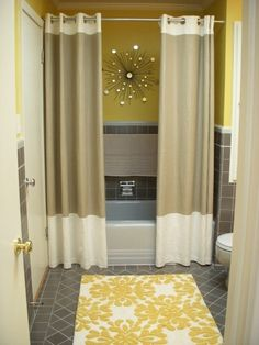Split shower curtain with wall art and floor rug for pop of color. cute ideas to add to a bathroom
