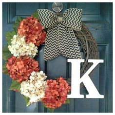 This gorgeous fall wreath has three seasonal orange hydrangeas with two cream hydrangeas attached to a grapevine wreath and tied with a black