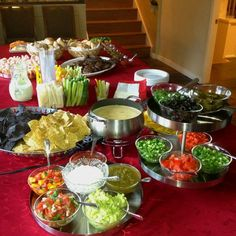 Taco bar/buffet...platters of different colored tortilla chips, tortillas and various toppings and salsas, guacamole, sour cream and different shredded cheeses, queso dip and prepared proteins(shrimp, fish, beef, pork, chicken)