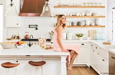 Lauren Conrad inside her bright rustic kitchen with subway backsplash, exposed wooden floating shelves, and a bronze stove hood