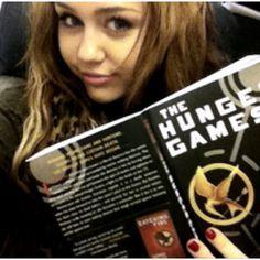 Miley reading The Hunger Games. Noooooooooooo! You are not worthy!!!!