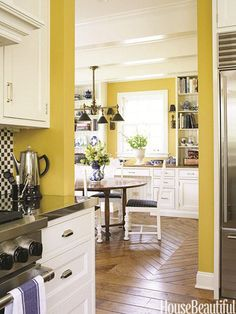 """This Benjamin Moore's """"Stuart Gold"""" color is the perfect against the white cabinets. How great are the walnut floors too?"""