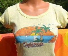 Tag: gone, copyright print by California LifestylesEra: 1981Fabric: soft ribbed 50-50Size reads: none, best fits modern Women's Medium or SmallMeasures: soft and stretchy 16 inches across the chest, 24 inches back collar to hemColors: pastel yellow scoop neck cap sleeve t-shirt with multicolor CALIFORNIA beach scene across the frontCondition: excellent vintage shape - soft and stretchy - lovelyFor reference, Tina over there measures 35-24-34.