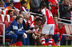 Walcott shares a word with Wenger after being replaced by Arsenal striker Olivier Giroud i...