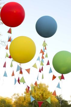 "A Pinner said, ""I wanted to really take advantage of being outdoors, and draw the eye up for the High Balloons party.  I positioned large round balloons (this time from Petite Party Studio) on the four corners of the dessert table, and draped fabric bunting from the balloons, creating a whimsical, lighter-than-air awning."""