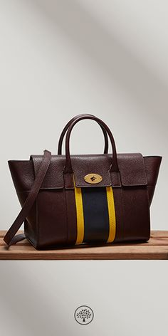 Shop the Bayswater with Strap at Mulberry.com in Oxblood, Lemon & Midnight Leather. The Bayswater is Mulberry's most iconic leather bag; its simple structure, timeless design and signature Postman's lock made it instantly popular. Its detachable shoulder strap gives greater versatility for an everyday wear. For the Summer '17 collection, Johnny Coca revisits the Bayswater with college stripe variations in colours characteristic of British school uniforms.
