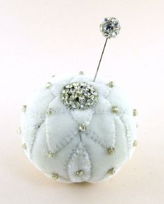 "2013 OOAK Janie Comito ~ Winter Velvet Pin Cushion with Rhinestone Button & Pin~ It snowed last night in Seattle, just enough to leave a sparkly sheen on everything this morning.  In celebration of snow time, Janie has created a winter pin cushion of white velvet.  It is handsewn with petal appliques decorated with pearl sheen glass beads, & a beautiful sparkly vintage rhinestone button perfectly matched by a stick pin with a sparkling rhinestone studded head created by Janie. 3"" W by 2 1/2"" H."