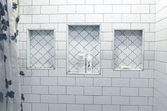 Arabesque tile of niche cubbies, in white subway tile shower. Simple with touch of elegance.