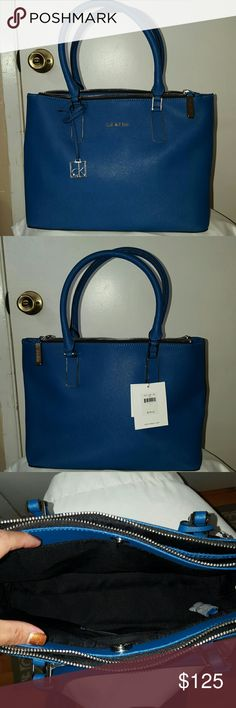"Calvin Klein Saffiano Leather Satchel NWT Calvin Klein Saffiano Leather Satchel in Blue. It has 3 major compartments.  1 compartment has a  makeup zippered pouch the other compartment has an id or cell phone pouch.    9""high, 12"" long, x 5"" wide Calvin Klein Bags Satchels"