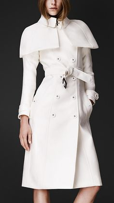 Burberry White Double Duchess Caped Trench Coat  The caped trench coat is a modern interpretation of an archive design.  Tailored in rich double duchess cotton silk, chosen for its understated lustre and texture, the silhouette is enhanced with an elegant canopy cape.  Signature cuff straps and a hook-and-eye neck closure complete the clean pared-down lines. ($2,595.00)