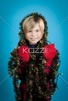 boy covered tinsel and christmas lights - Young boy covered in tinsel and Christmas lights on a blue background. Model: Josh Chapman
