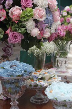 Arranjo em tons de rosa, lilás e azul. Forminhas de tecido em diferentes estampas.