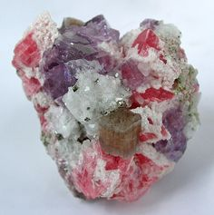 This beautiful mineral specimen is from a recent find at the Wudong Mine of China. It features several minerals: apatite in the middle sits front and center on cherry-red rhodochroite rhombs. The purple cubes are fluorite crystals and the small metallic-looking cubes are pyrite. Everything is surrounded by quartz crystals.