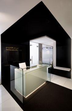 reception desk. black wrap around. contemporary office design. neutral palette. black white grey interiors