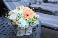 white hydrangea, roses, peach gerbera, peach ranunculus, and chamomile in a birch cube