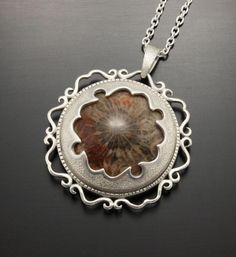 Fossil coral and sterling silver.  It's fabricated by hand  Kazuhiko Ichikawa
