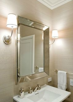 source: Sutro Architects Amazing bathroom with sand grasscloth wallpaper with crisp white bathroom crown molding. Restoration Hardware Venetian Beaded Mirror flanked by Visual Comfort Lighting Vendome Sconces and glossy white pedestal sink.