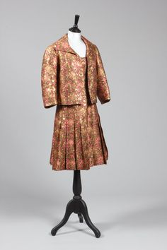 Chanel haute couture brocaded silk and gold lame cocktail ensemble, 1960, labelled to the jacket and numbered 13213, of rich Bianchini pink and gold Mughal inspired brocade, comprising: cocktail dress with empire-line bodice and broad waistband, box pleated skirt, the loose jacket lined in raspberry silk with chain weighted hem and no fastenings