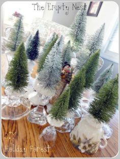 how to make glass glittered bottle brush trees. I love how they are set into crystal candlestick holders.