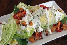 Wedge Salad with bacon, chives, croutons and blue cheese dressing! usually this salad is plated, but I love it on this platter! it would look fabulous on a buffet.  #entertaining #salad #presentation