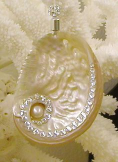 "Silver Abalone with Swarovski Crystals Ornament - Bring a beach feel to your tree with this beautiful silver abalone shell encrusted with hand-placed Swarovski crystals and a large freshwater pearl. The ornament hangs from a silk cord and silver-plated end cap and is topped with a rhinestone ball. Shell measures 2""-2.5"" long - cording adds about 1"". ($25.00)"