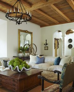 Living Room by Katherine Shenaman Interiors // peck cypress, arches, beams, turquoise pillows, wood square coffee table, rustic chandelier, brass mirror, shell pot, moss balls