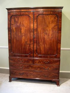 A very fine George III period figured mahogany linen press of rare proportion, (being both shallow and low waisted). With boxwood inlayed cornice and shaped panel doors enclosing five sliding trays, over graduated oak lined drawers and original splay bracket feet. Original brass handles, locks, and double panelled back. Circa 1785.