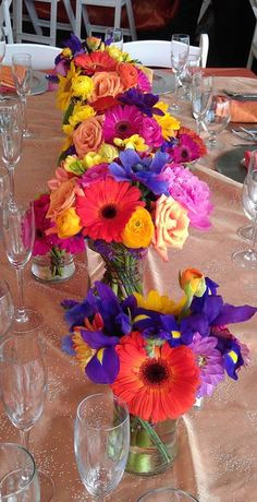 Brightly Colored Gerbera Daisies Ranunculus Zinnias Iris make a fun tablescape for a wedding