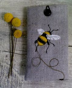 Machine embroidered linen bumble bee phone case, fully lined and finished with a hoop and button. hand made by Shropshire based designer Suzanne Bates