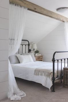 This cozy sleeping nook was created by adding a faux wood beam and lace curtains over the bed, and the results are amazing!