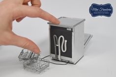 A dishwasher with opening door, 2 pull out hand  soldering metal racks, metal hinges, magnet door latch, metal cover. Made by me in 1:12 scale.